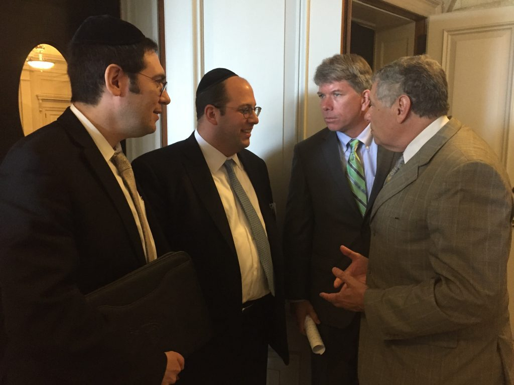 (L-R) Lakewood Mayor Menashe Miller, Rabbi Avi Schnall of Agudath Israel, Assemblyman Sean Kean and Senator Bob Singer discussing the busing bill in Trenton in June.