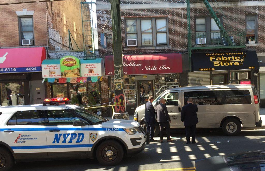 Police detectives gather residence from the victim's vehicle. (Yosef Caldwell/Hamodia)
