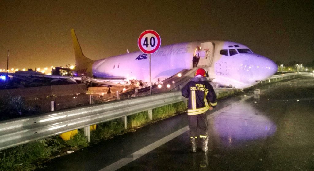 A firefighter stands in front of a cargo plane that exited the runway after landing and slid onto a local road in Orio al Serio, next to Milan, Italy, in this August 5, 2016 handout picture provided by Italy's Fire Fighters. Vigili del Fuoco/Handout via REUTERS ATTENTION EDITORS - THIS IMAGE WAS PROVIDED BY A THIRD PARTY. EDITORIAL USE ONLY.