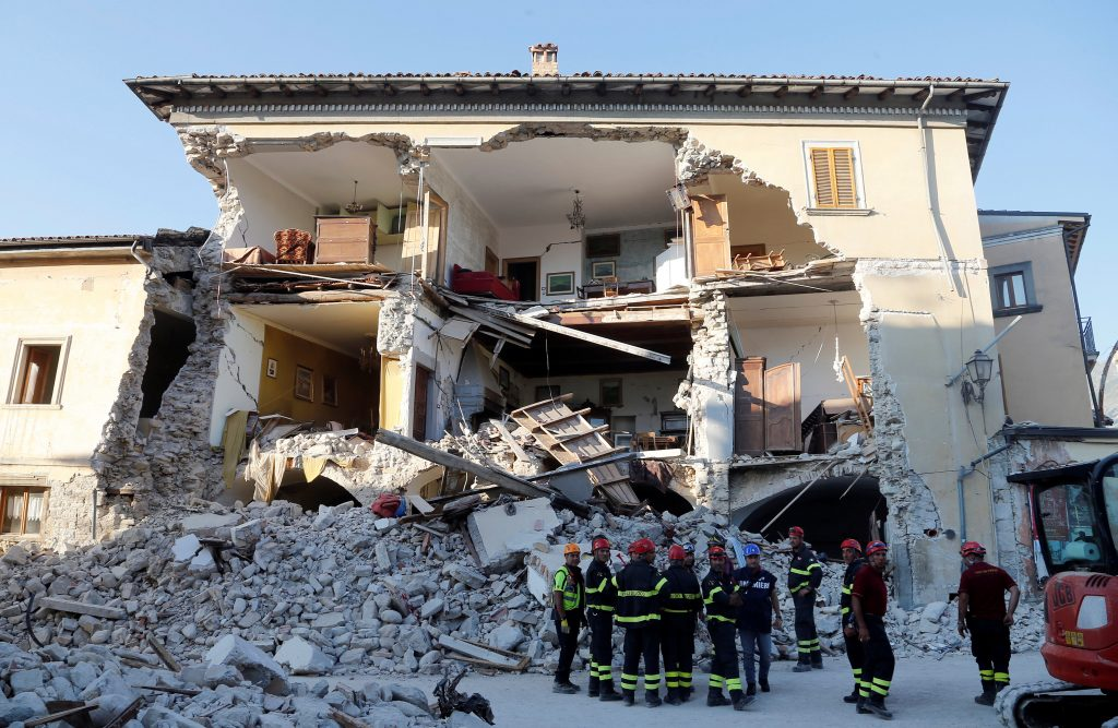 Firefighters stand next to a collapsed house following an earthquake in Amatrice, central Italy, August 27, 2016. REUTERS/Ciro De Luca
