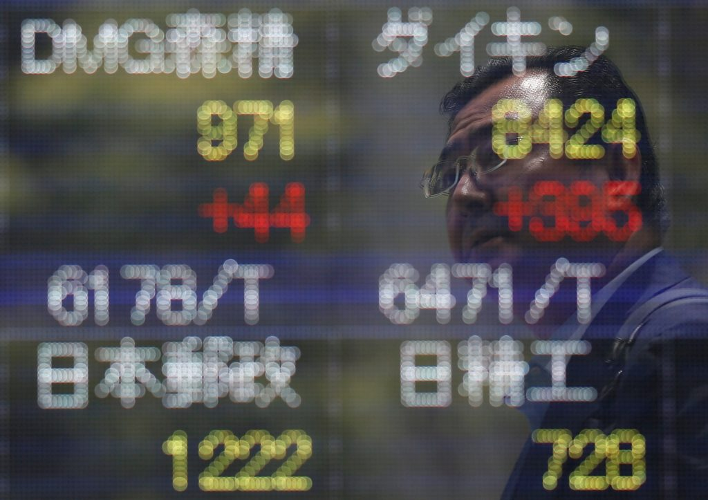 A man is reflected on a stock quotation board outside a brokerage in Tokyo, Japan July 11, 2016. REUTERS/Issei Kato/File Photo