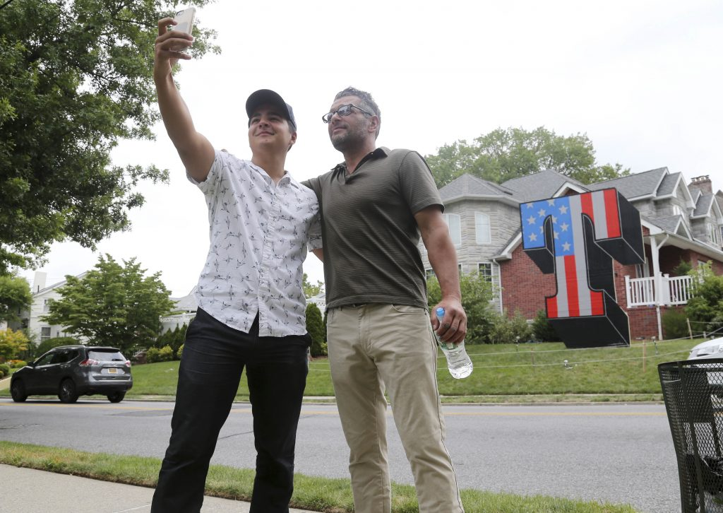 """Mitchell Hotchkiss, left, takes a picture with Scott LoBaido in front of a large """"T"""" that LoBaido designed and built in Staten Island. (AP Photo/Seth Wenig)"""