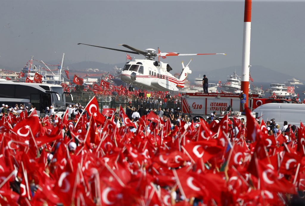 A helicopter flies over as people wave Turkey's national flags during the Democracy and Martyrs Rally, organized by Turkish President Tayyip Erdogan and supported by ruling AK Party (AKP), oppositions Republican People's Party (CHP) and Nationalist Movement Party (MHP), to protest against last month's failed military coup attempt, in Istanbul, Turkey, August 7, 2016. REUTERS/Osman Orsal