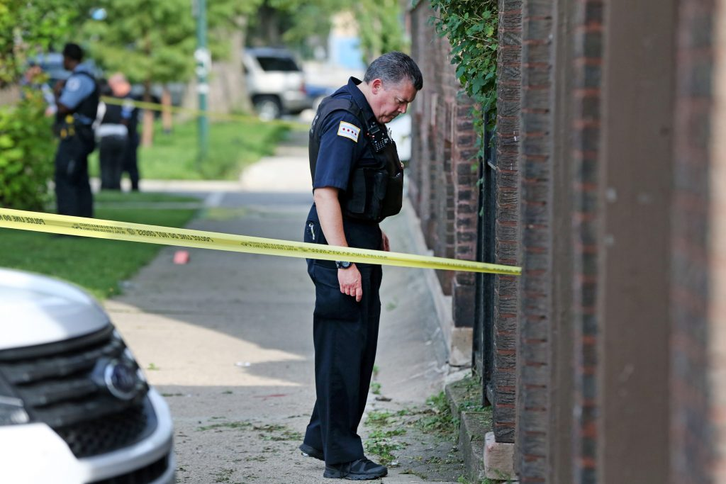 Members of the Chicago Police department investigate a shooting scene in the 5600 block of South Campbell Ave. (Nuccio DiNuzzo/Chicago Tribune/TNS)