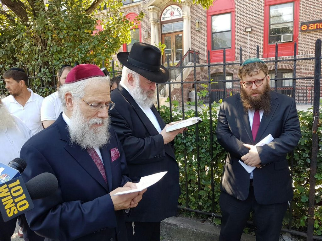 Norman Rosenbaum (in black hat) davening on Friday at the scene of his brother Yankel's murder 25 years ago, in front of the St. Marks School on President St. and Brooklyn Ave. in Crown Heights. Also pictured are (left foreground) Rabbi Shea Hecht and (right) Rabbi Yaacov Behrman. (Schnear Erlich)