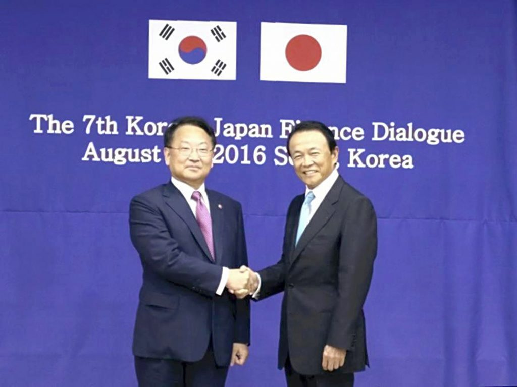 Japanese Finance Minister Taro Aso, right, and South Korea's Strategy and Finance Minister Yoo Il Ho shake hands in Seoul on Saturday. (Munenori Inoue, The Japan News-Yomiuri)