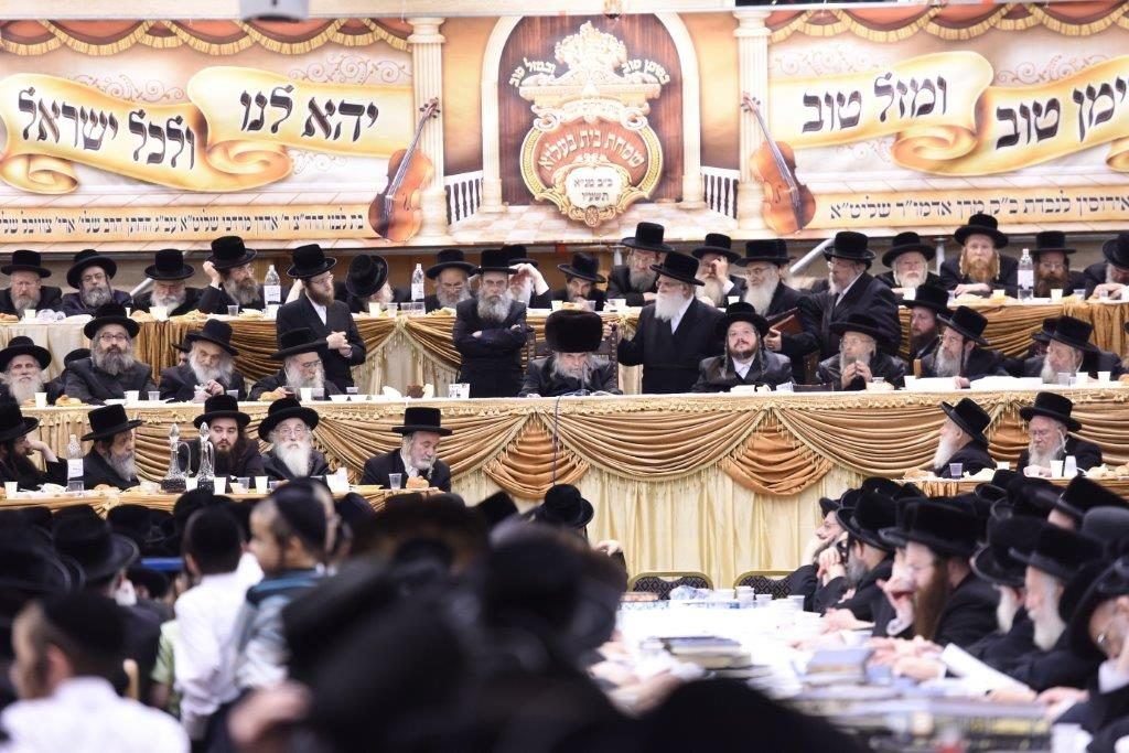 The Belzer Rebbe (C) speaks at the yahrtzeit tisch. (Moshe Goldstein)