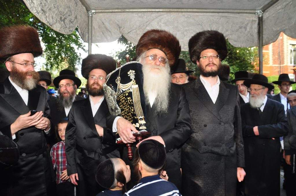 Reb Dovid Adler holds the sefer Torah under the chuppah during the procession. (Lawrence Purcell)
