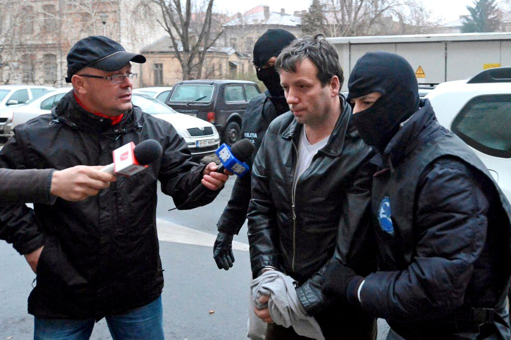 Marcel Lazar Lehel is escorted by masked policemen in Bucharest, Romaniaafter being arrested in Arad, 337 miles west of Bucharest, in January 2014. (Reuters/Mediafax/Silviu Matei/File)
