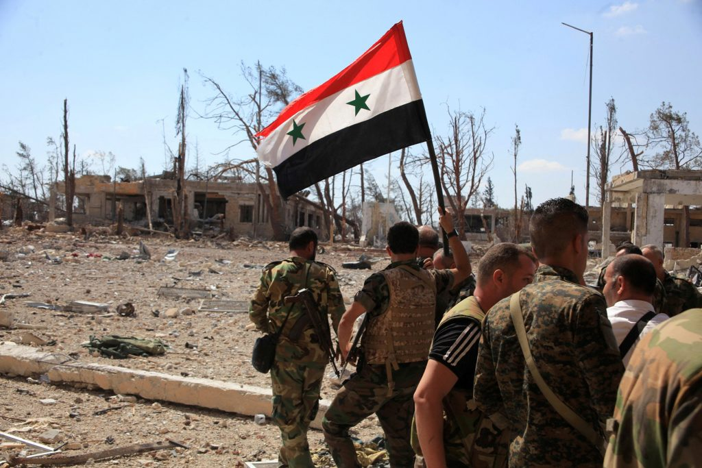 (SANA/Handout via REUTERS) Forces loyal to Syria's President Bashar al-Assad walk at a military complex as one of them holds up a Syrian national flag, after they recaptured areas in southwestern Aleppo on Sunday that rebels had seized last month, Syria.