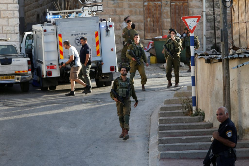 Israeli forces gather near the scene of a stabbing attack by a Palestinian terrorist, in Tal-Rumida, Chevron. (Mussa Qawasma/Reuters)