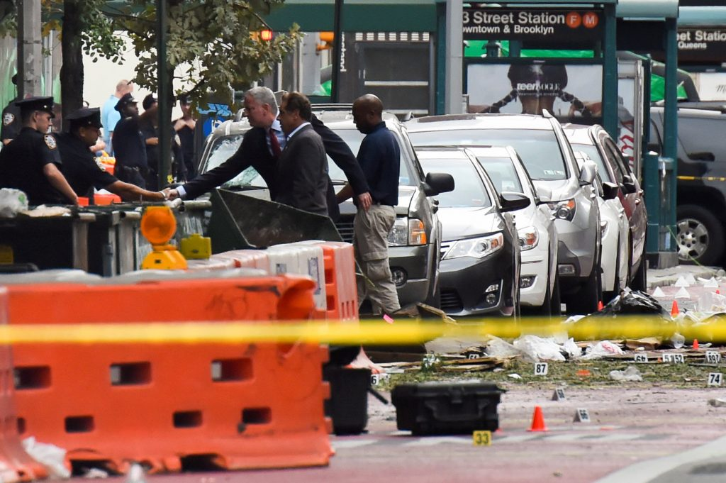 With New York Governor Andrew Cuomo alongside, New York Mayor Bill de Blasio, seen here shaking hands with a policeman, surveys the site of an explosion which occurred in the Chelsea neighborhood of New York. (Rashid Umar Abbasi/Reuters)