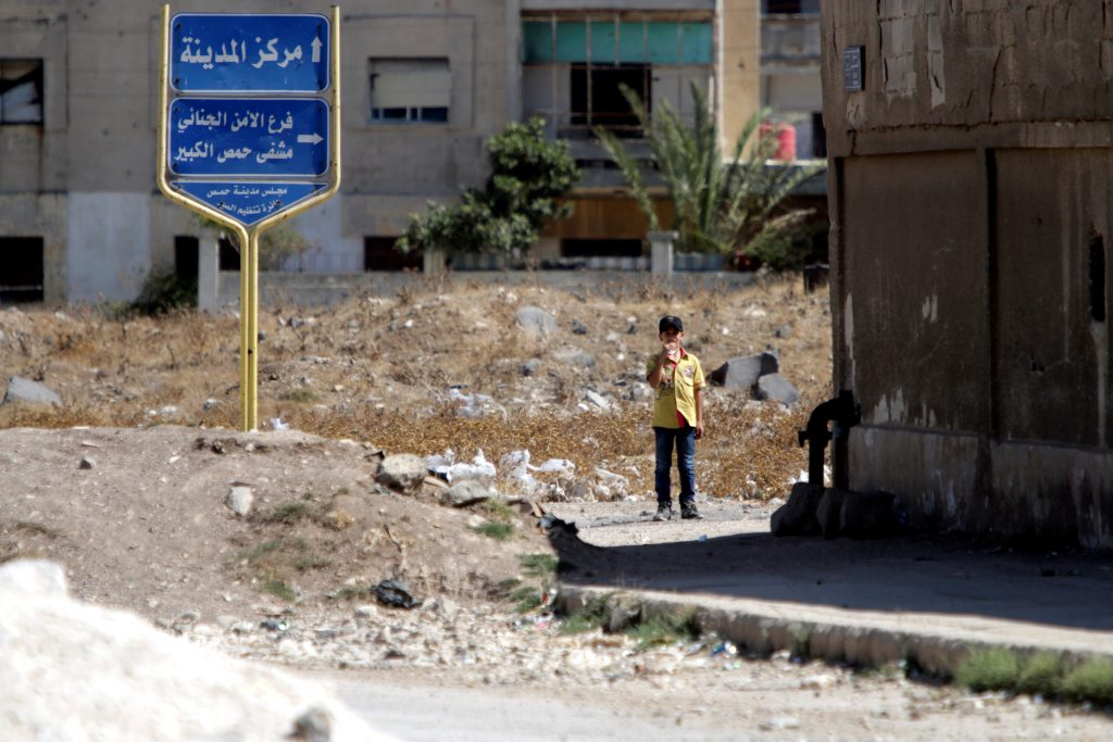A boy stands near the entrance of the Waer district in the central Syrian city of Homs, Syria. (Omar Sanadiki/Reuters)
