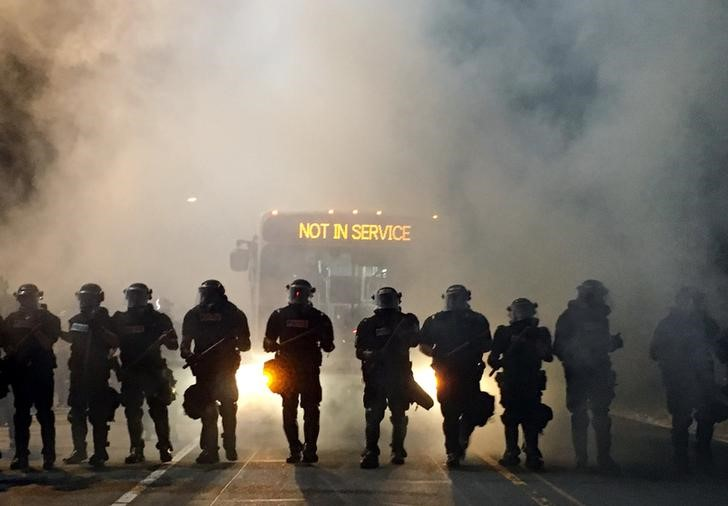 Police officers wearing riot gear block a road during protests after police fatally shot Keith Lamont Scott in the parking lot of an apartment complex in Charlotte, North Carolina. (Adam Rhew/Charlotte Magazine/Reuters)