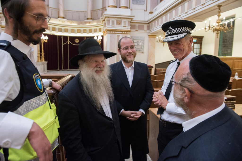 Sir Bernard (R) with Rabbi Hershel Gluck (C), and members of Shomrim in the Bobov Shul in Stamford Hill. (Shomrim)