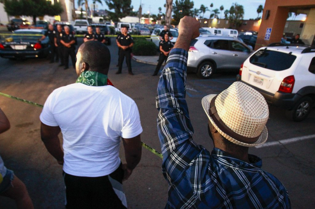 One man holds his fist up as others yell at police at the scene where a black man was shot by police earlier in El Cajon, east of San Diego, Calif., Tuesday, Sept. 27, 2016. (Hayne Palmour IV/The San Diego Union-Tribune via AP)