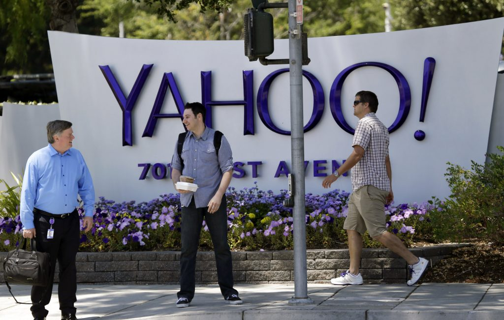 FILE - People walk in front of a Yahoo sign at the company's headquarters in Sunnyvale, Calif. (AP Photo/Marcio Jose Sanchez, File)
