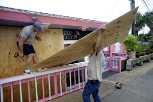 Tim Allen, left, and Joe Allen board up the front of an outdoor bar as they prepare for Tropical Storm Hermine in Cedar Key, Fla., on Thursday. (AP Photo/John Raoux)