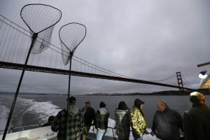 A group of veterans stand on the Salty Lady charter boat while heading out under the Golden Gate Bridge at dawn to go salmon fishing near San Francisco. (AP Photo/Eric Risberg)