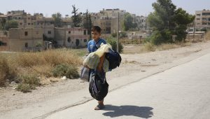 A boy carries his belongings as he leaves the Moadamiyeh on Friday. (AP Photo)