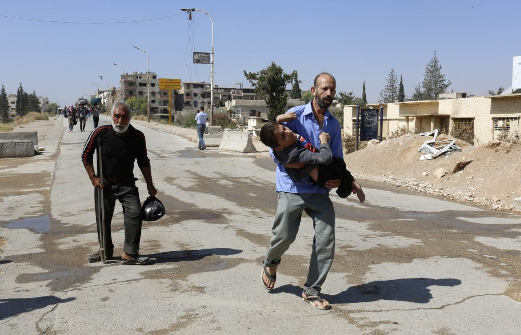 Civilians leave the Moadamiyeh on Friday. (AP Photo)