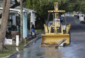 Clears debris from the street in Cedar Key, Fla., on Friday. (AP Photo/John Raoux)
