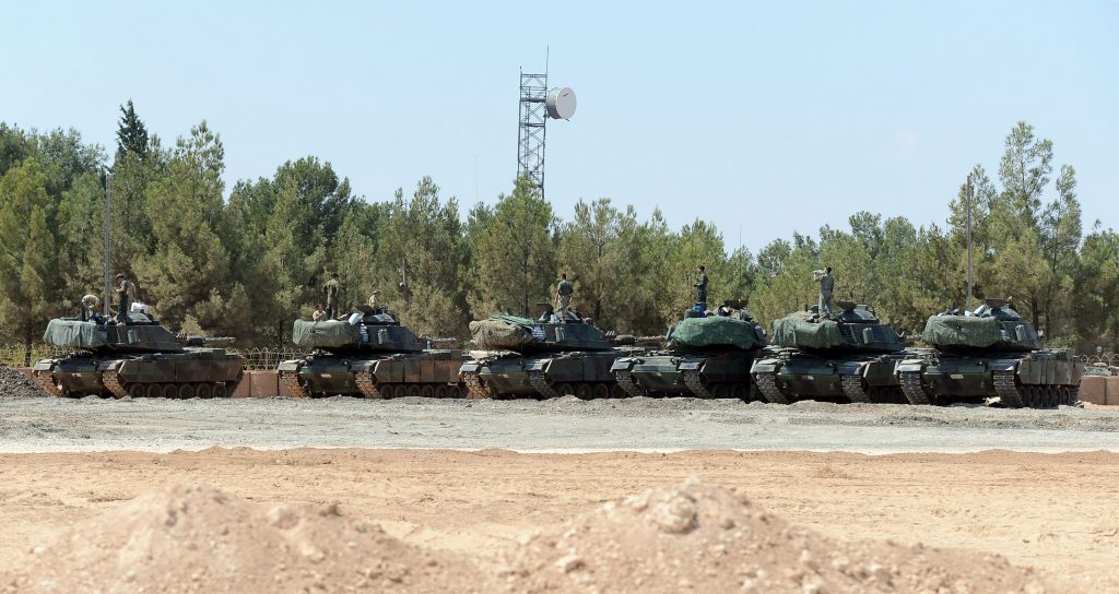 "Turkish tanks stationed near the Syrian border, in Karkamis, Turkey, Saturday, Sept. 3, 2016. Turkey's state-run news agency says Turkish tanks have entered Syria's Cobanbey district northeast of Aleppo in a ""new phase"" of the Euphrates Shield operation. Turkish tanks crossed into Syria Saturday to support Syrian rebels against the Islamic State group, according to the Anadolu news agency. (Ismail Coskun, IHA via AP)"