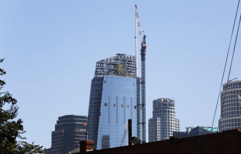 A 160-foot spire is seen atop the Wilshire Grand Tower building after a crane hoisted it into place early Saturday, Sept. 3, 2016, in downtown Los Angeles. The 10-ton spire makes the building the tallest building west of the Mississippi River. It's now 1,099 feet high, 81 feet higher than the nearby U.S. Bank Tower, lower right, which held the tallest building record since 1989. The $1-billion hotel and office complex is scheduled to open next March. (AP Photo/Reed Saxon)