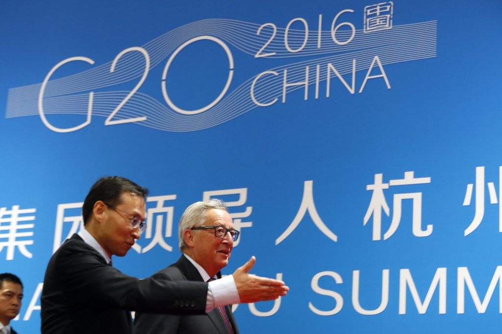 European Commission President Jean-Claude Juncker, right, is shown the way by a Chinese official as he arrives at the G20 Summit in Hangzhou in eastern China's Zhejiang province, Sunday, Sept. 4, 2016. European Union leaders have called for China to take action on its bloated steel industry and defended an order to Ireland to collect back taxes from Apple, highlighting the trade strains looming over a global economic summit.(AP Photo/Ng Han Guan)