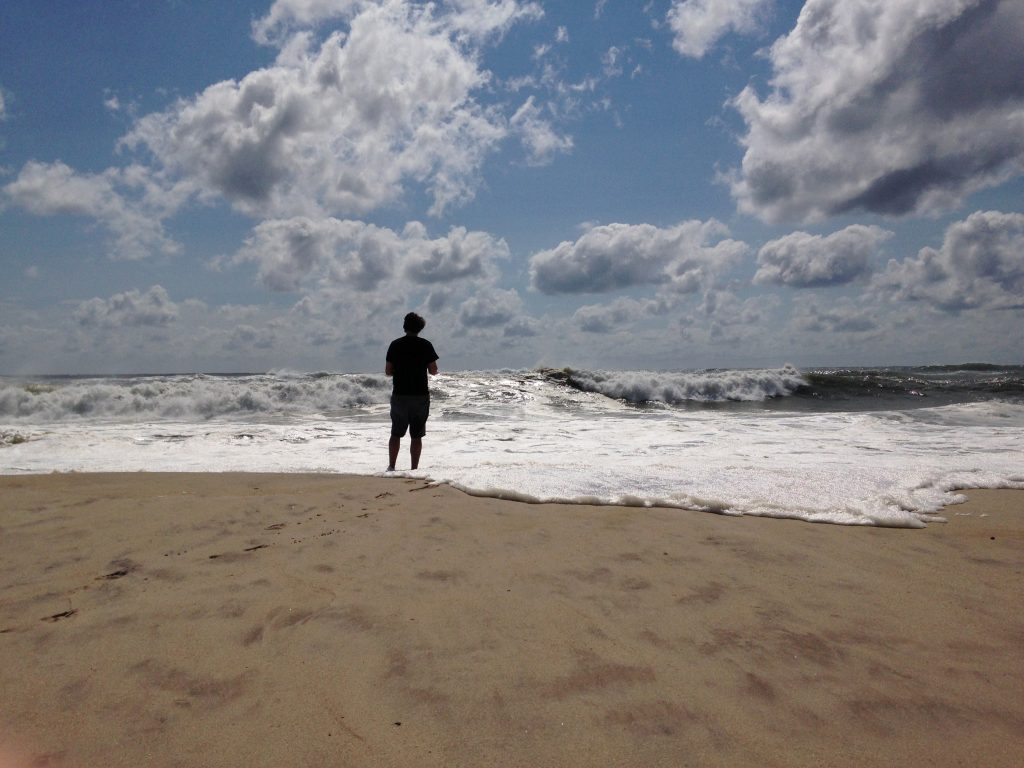 A man stands at the edge of the water on the beach in Bridgehampton, N.Y., on the southeastern shore of Long Island, on Sunday. (AP Photo/Jennifer Peltz)