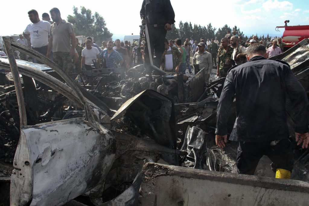 Syrian security forces, emergency services and residents look at the remains of burned vehicles at the site of a bombing in Tartus, Syria, on Monday. (SANA via AP)