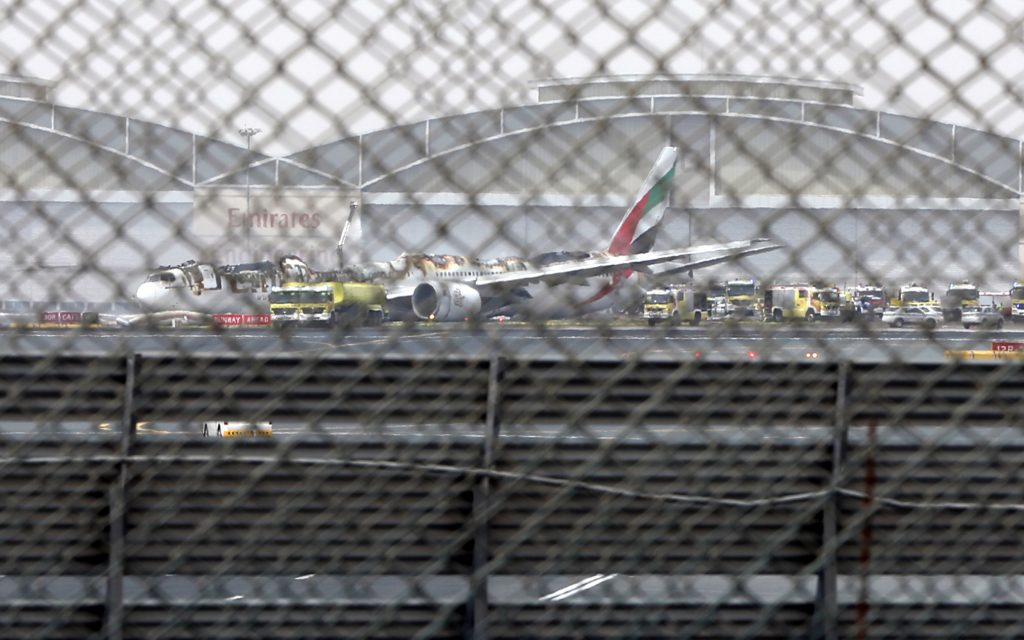 FILE- In this Wednesday, Aug 3, 2016 file photo, a damaged Boeing 777 is seen at the Dubai airport after it crash-landed, in Dubai, United Arab Emirates. A preliminary report into last month's Emirates airliner crash landing in Dubai has found that the pilot attempted to abort the landing after an initial touchdown and that the plane ultimately hit the runway as its landing gear was retracting. (AP Photo/Jon Gambrell, file)