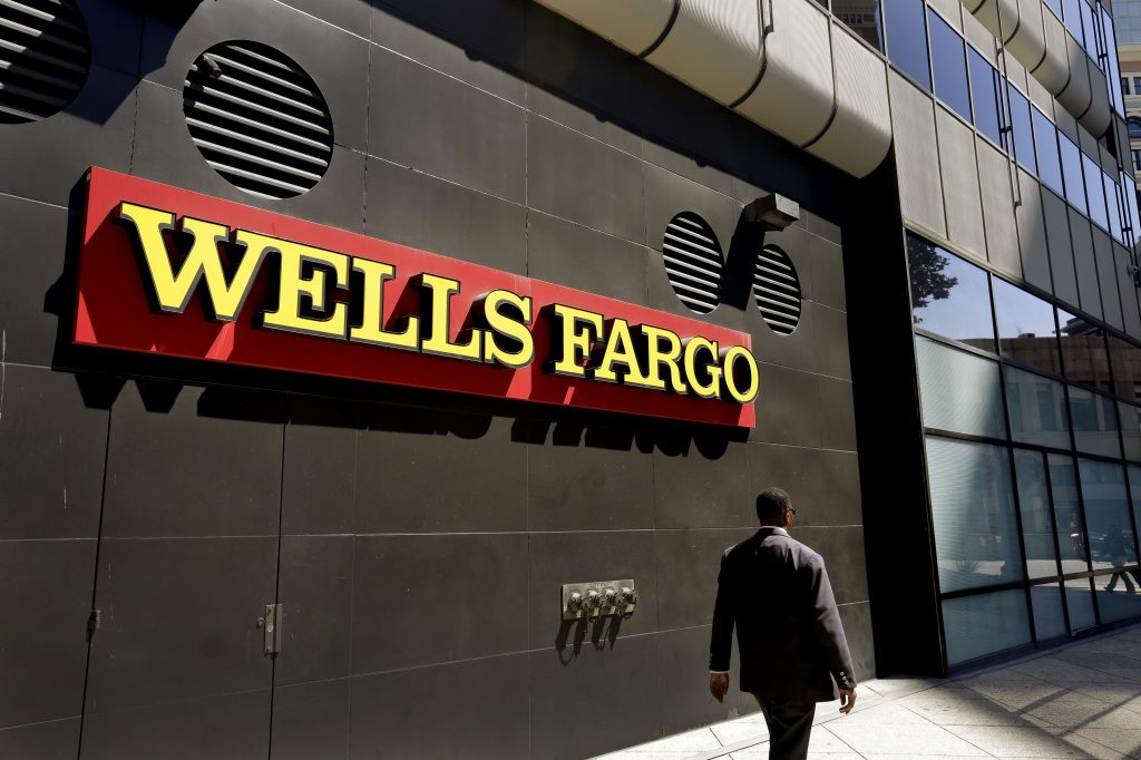 FILE - In this July 14, 2014, file photo, a man passes by a Wells Fargo bank office in Oakland, Calif. (AP Photo/Ben Margot, File)