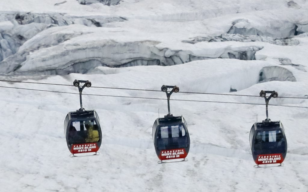 Aerial view, Friday, Sept. 9, 2016, of three cars of the Panoramic Mont Blanc cable car where tourists were trapped after it stalled around 4 p.m. (1400 GMT) on Thursday, when its cables reportedly tangled. The cable car carrying tourists stopped working at high altitude over the Mont Blanc massif in the Alps on Thursday, prompting a major rescue operation and leaving 45 people trapped in midair overnight, France's interior minister said. (AP Photo/Luca Bruno)