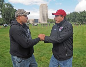 Standing Rock Sioux tribal chairman Dave Archambault II, right, greets Wayland Gray, of Muskogee Creek Hickory Ground, Okla., at an organized protest on the North Dakota state capitol grounds on Friday, Sept. 9, 2016 in Bismarck, N.D. (Tom Stromme/The Bismarck Tribune via AP)