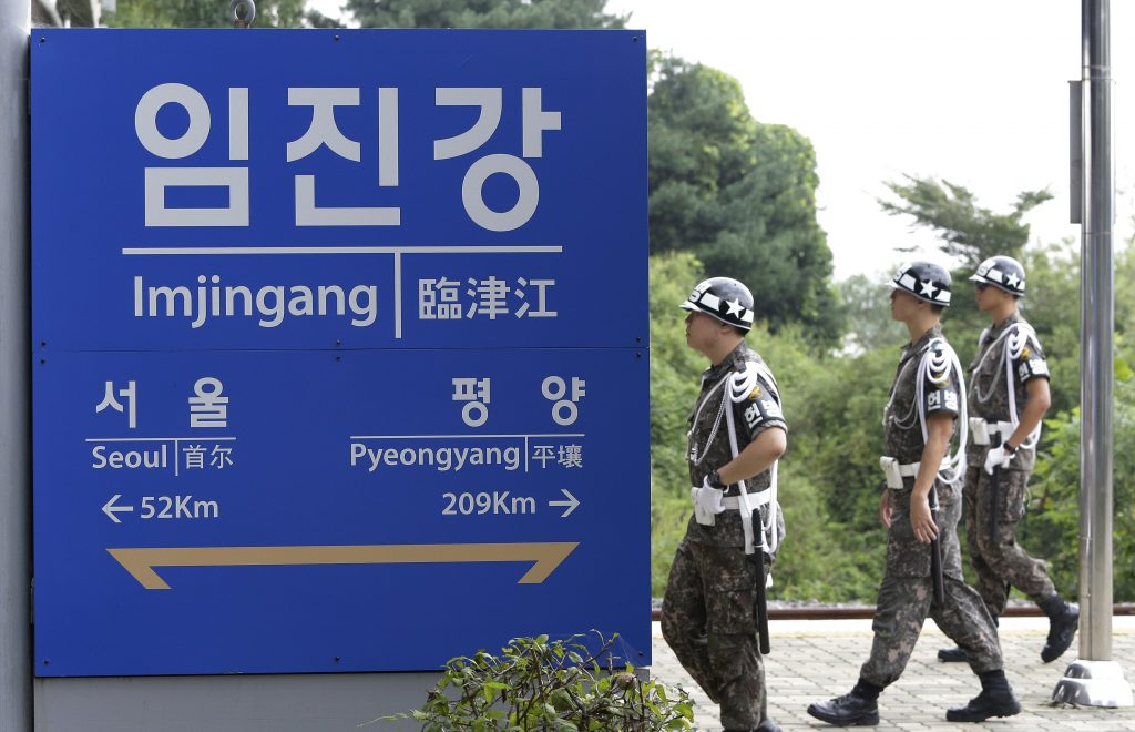 """South Korean army soldiers walk by a signboard showing the distance to the North Korean capital Pyongyang and to South's capital Seoul from Imjingang Station near the border village of the Panmunjom in Paju, Sunday, Sept. 11, 2016. The U.N. Security Council is strongly condemning North Korea's latest nuclear test and says it will start discussions on """"significant measures"""" against Pyongyang including new sanctions. (AP Photo/Ahn Young-joon)"""
