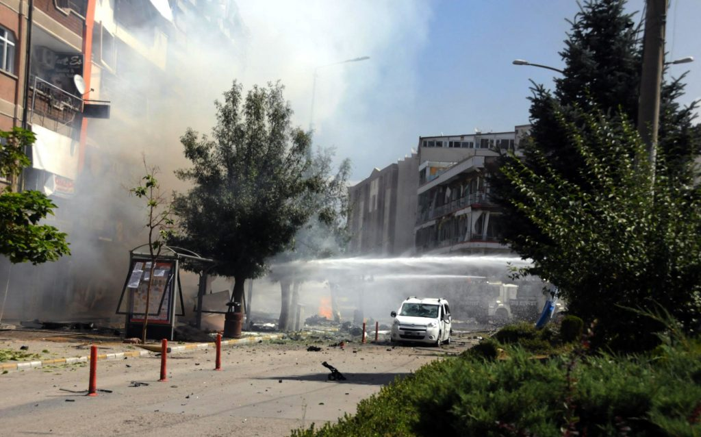 Firefighters work to extinguish a fire after a car bomb attack in the city center of Van, eastern Turkey, Monday, Sept. 12, 2016. Turkey's state-run Anadolu news agency says an explosion near the ruling party headquarters and the governor's office in the eastern province of Van has left several wounded. The explosion occurred Monday morning on the first day of Eid al-Adha, an Islamic holiday.(DHA via AP)