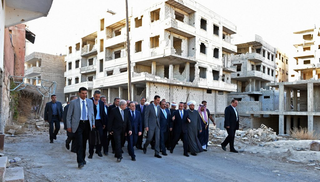 "In this photo released by the Syrian official news agency SANA, Syrian President Bashar Assad, center, walks on a street with officials after performing the morning Eid al-Adha prayers in Daraya, a blockaded Damascus suburb, Syria, Monday, Sept. 12, 2016. Syrian President Bashar Assad says his government is determined to ""reclaim every area from the terrorists, and to rebuild"" the country. His remarks came just hours ahead of the start of a cease-fire brokered by the United States and Russia. (SANA via AP)"