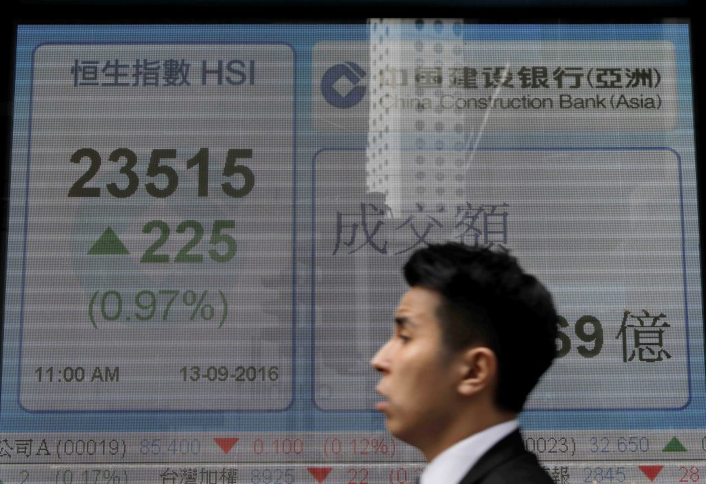 A man walks past an electronic board showing Hong Kong share index outside a local bank in Hong Kong, Tuesday, Sept. 14, 2016. Asian stocks were mostly higher on Tuesday after a Federal Reserve board member said she was in no hurry to raise interest rates, reassuring investors who were worried that the rate hike could pull share prices lower. (AP Photo/Vincent Yu)