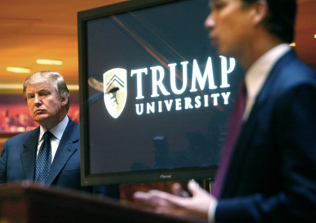 Donald Trump (L) listens as Michael Sexton introduces him at a news conference in New York, where he announced the establishment of Trump University, in 2005. (AP Photo/Bebeto Matthews, File)