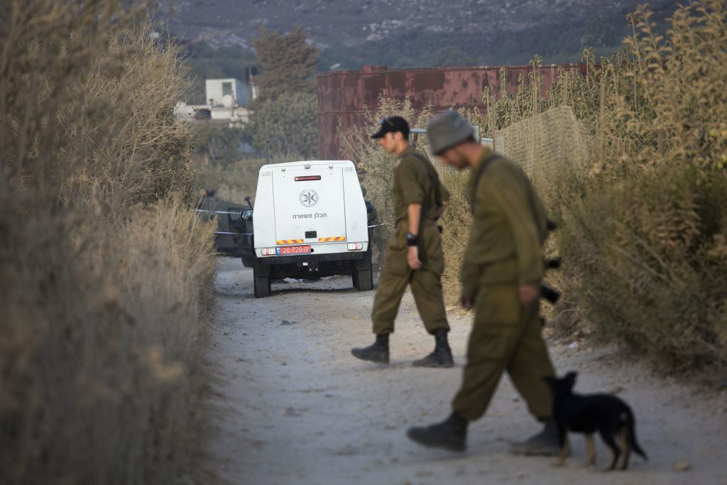 Israeli soldiers secure a road leading to where projectiles fired from Syria hit the Israeli-controlled part of the Golan Heights, near Majdal Shams, Tuesday, Sept. 13, 2016. The Israeli military struck artillery positions in Syria on Tuesday after a projectile from that country's civil war hit the Israeli-controlled part of the Golan Heights, but denied a Syrian claim that Syrian forces shot down two Israeli aircraft. (AP Photo/Ariel Schalit)