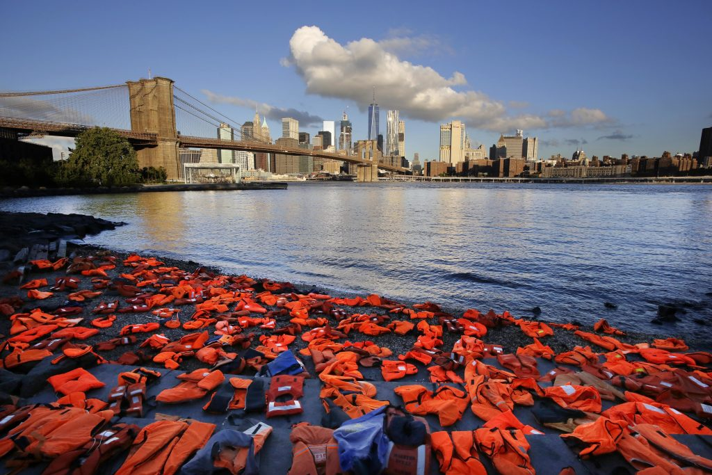 Advocates with Oxfam America have placed hundreds of life jackets on the ground along the New York City waterfront to draw attention to the refugee crisis, Friday, Sept. 16. (AP Photo/Mark Lennihan)