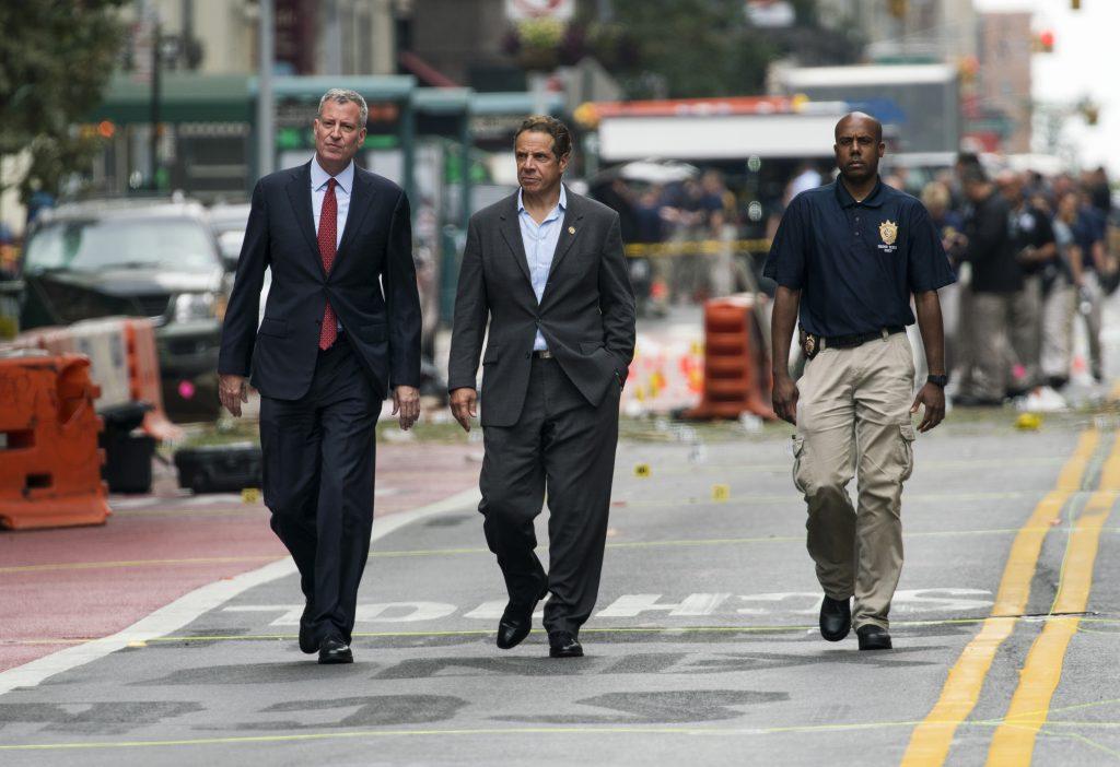 New York City Mayor Bill de Blasio, left, and New York Gov. Andrew Cuomo, center, walk near the scene of the explsoion on Sunday morning.  (AP Photo/Craig Ruttle)