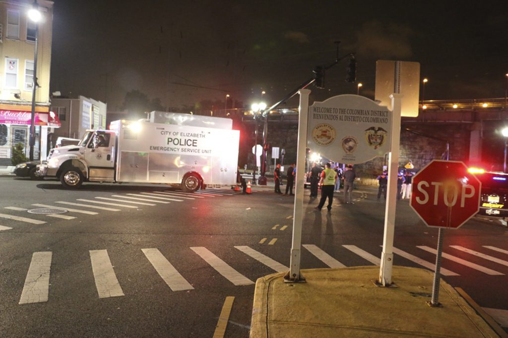 Bomb squad personnel stand around the scene of an explosion near the train station, early Monday, Sept 19, 2016, in Elizabeth, N.J. A suspicious device found Sunday night in a trash can near a New Jersey train station exploded early Monday as a bomb squad robot attempted to disarm it. (Jessica Remo/NJ Advance Media via AP)