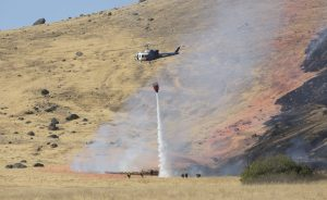 A California Highway Patrol helicopter drops water on a fire caused by the crash of a U.S. Air Force U-2 spy plane in the Sutter Butte Mountains, Tuesday. (AP Photo/Rich Pedroncelli)