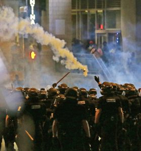 Police fire tear gas as protestors converge downtown following Tuesday's police shooting of Keith Lamont Scott in Charlotte, N.C. (AP Photo/Gerry Broome)
