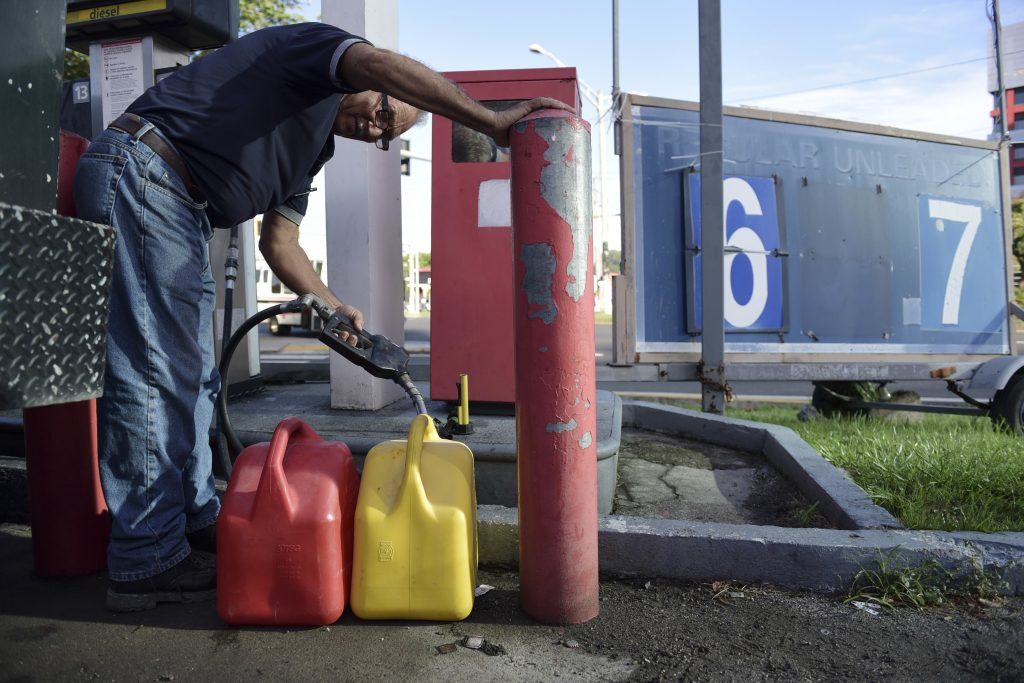 Ismael Ortiz fills his gas containers with diesel, in San Juan, Puerto Rico, Thursday, Sept. 22, after a massive blackout hit Puerto Rico Wednesday afternoon, leaving at least 1.5 million people without power overnight and into the following day. (AP Photo/Carlos Giusti)