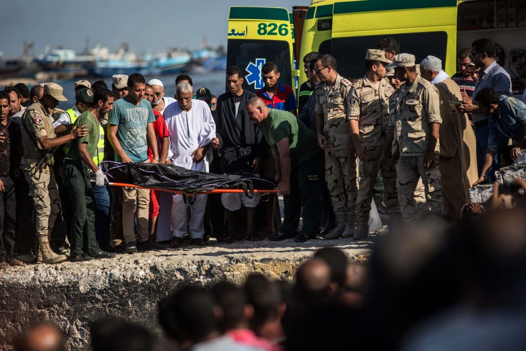 Egyptian Coast Guard and rescue workers bring a body ashore in Rosetta, Egypt, on Thursday. (AP Photo/Eman Helal)