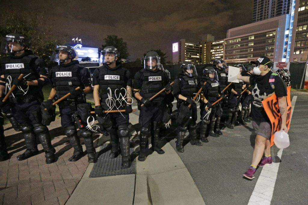A protester walks in front of a line of police officers blocking the access road to I-277 on the third night of protests in Charlotte, N.C. Thursday, Sept. 22, 2016, following Tuesday's fatal police shooting of Keith Lamont Scott. (AP Photo/Chuck Burton)