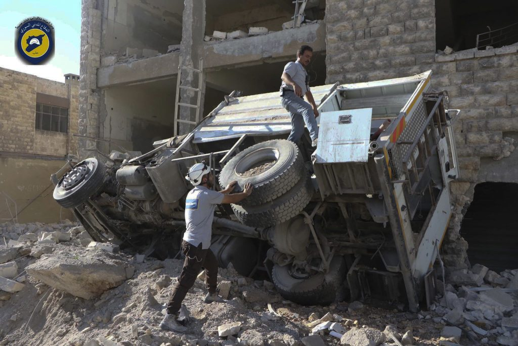 Rescue workers remove a destroyed ambulance outside the Syrian Civil Defense headquarters on Friday. (Syrian Civil Defense White Helmets via AP)